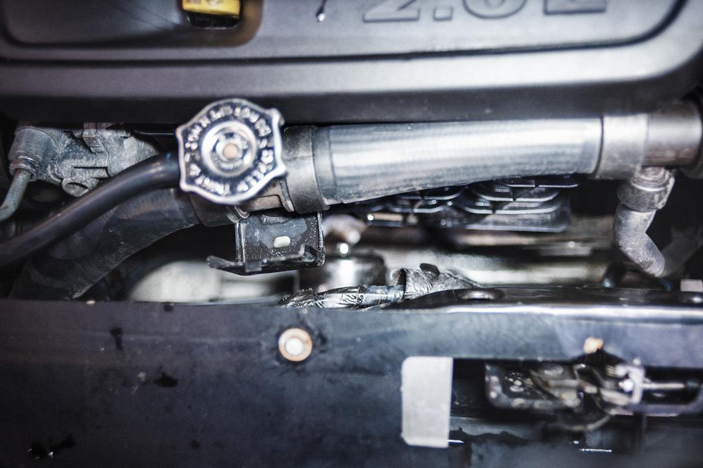 Откручиваем кронштейн верхнего патрубка радиатора